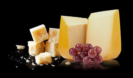 Variété de fromages avec grappe de raisins rouges.