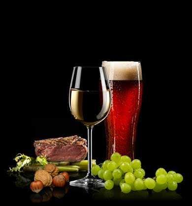 A glass of white wine, glass of dark beer with foam, and a sliced piece of grilled beef.