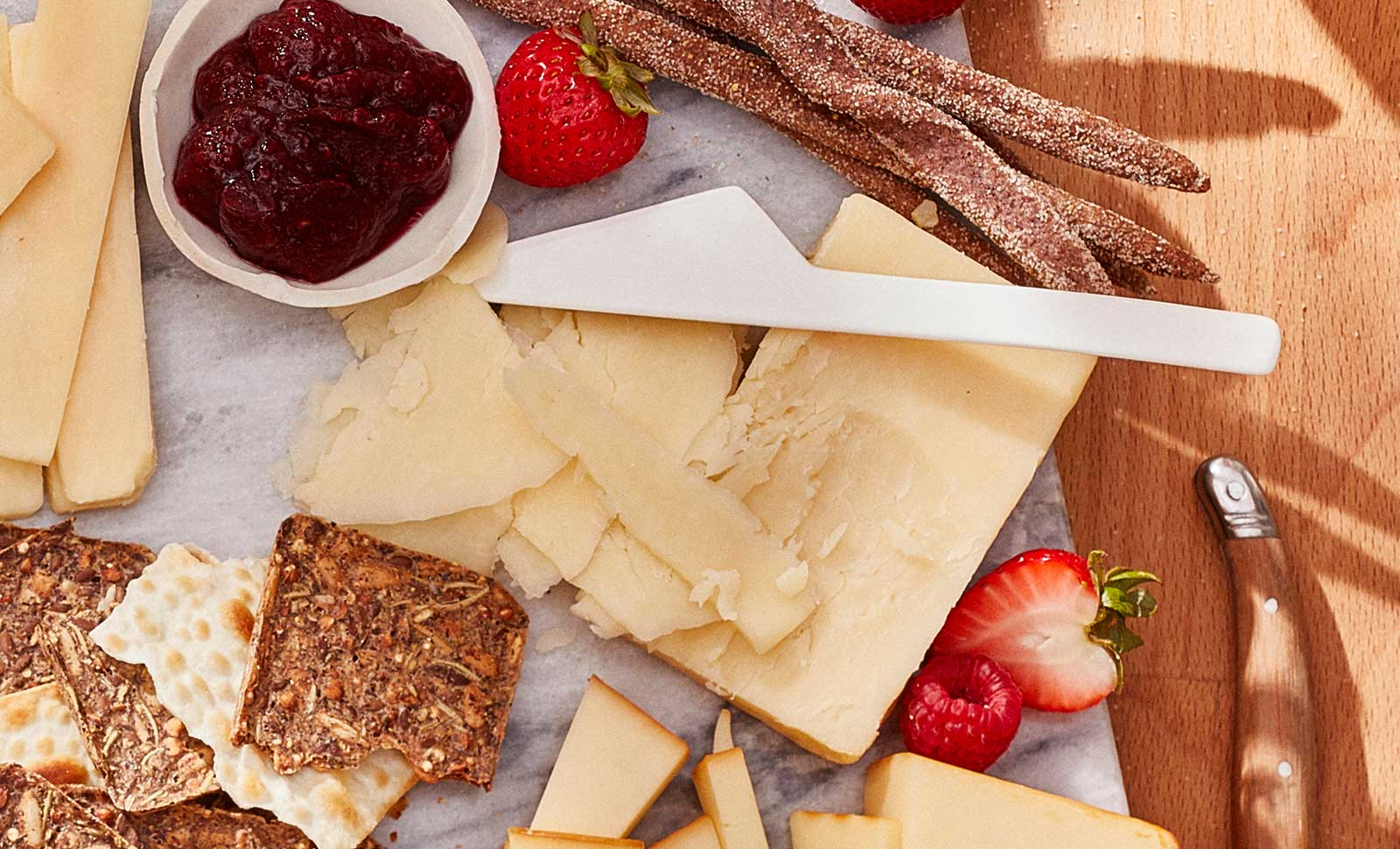 Two-year naturally aged cheddar cut with a knife served with multigrain crackers and strawberries.