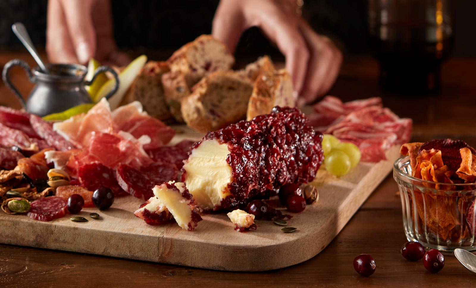 A pair of hands preparing a wooden board with cheddar cheese with cranberry log, assorted sliced meats, fruits and breads.