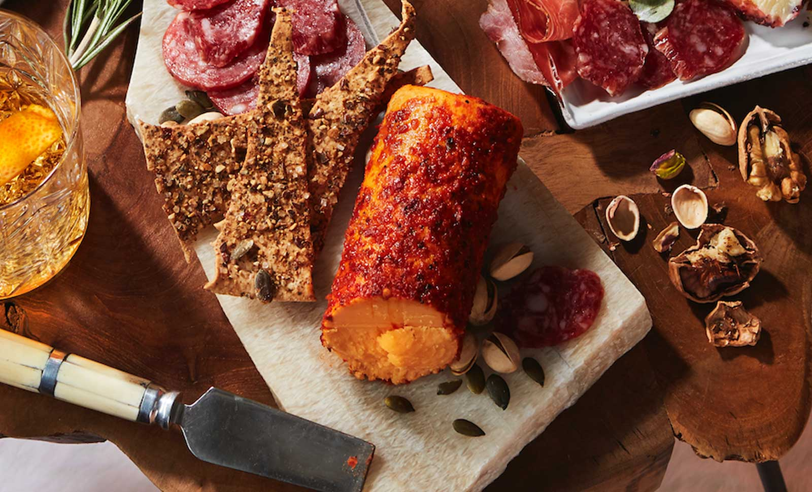 A Piri Piri Seasoned Cheddar Log surounded by an assortment of nuts, charcuterie and crackers