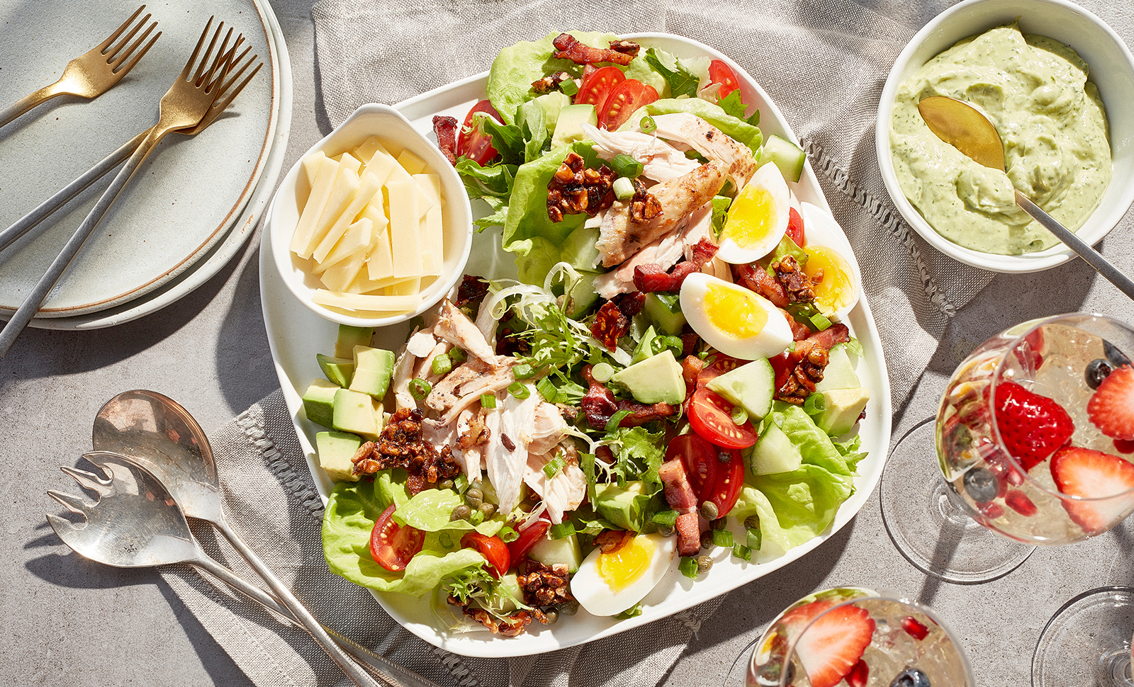 A colorful brunch salad made of mixed greens, sliced eggs, avocado cubes, tomatoes with a small bowl of sliced cheese.