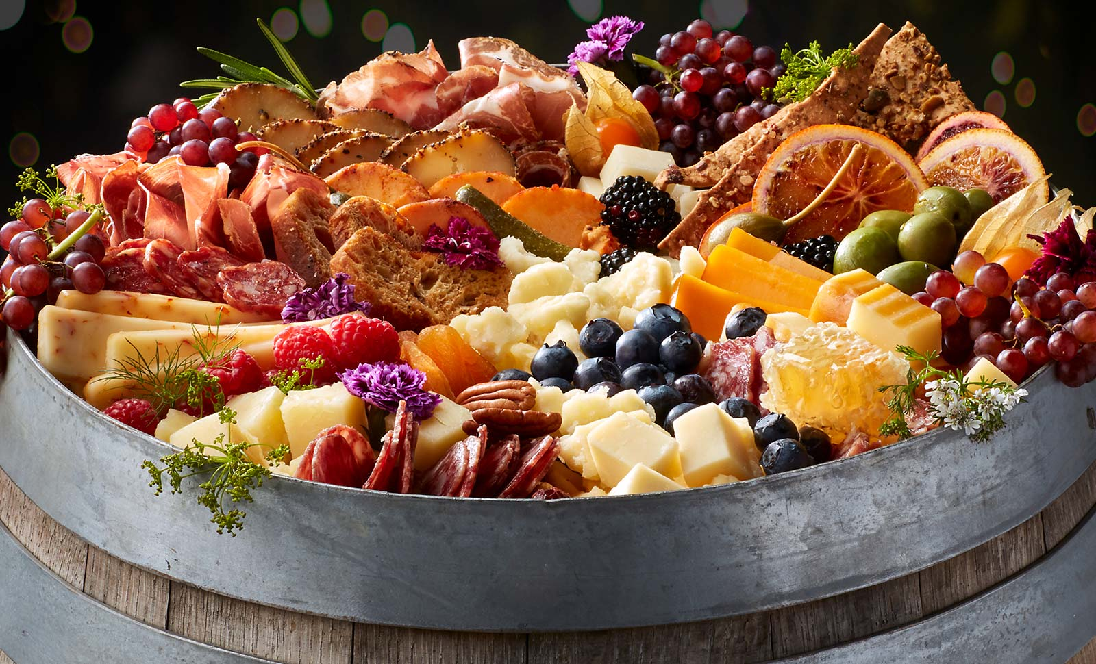 A wooden barrel topped with an assortment of cheeses, meats, fruits and breads.