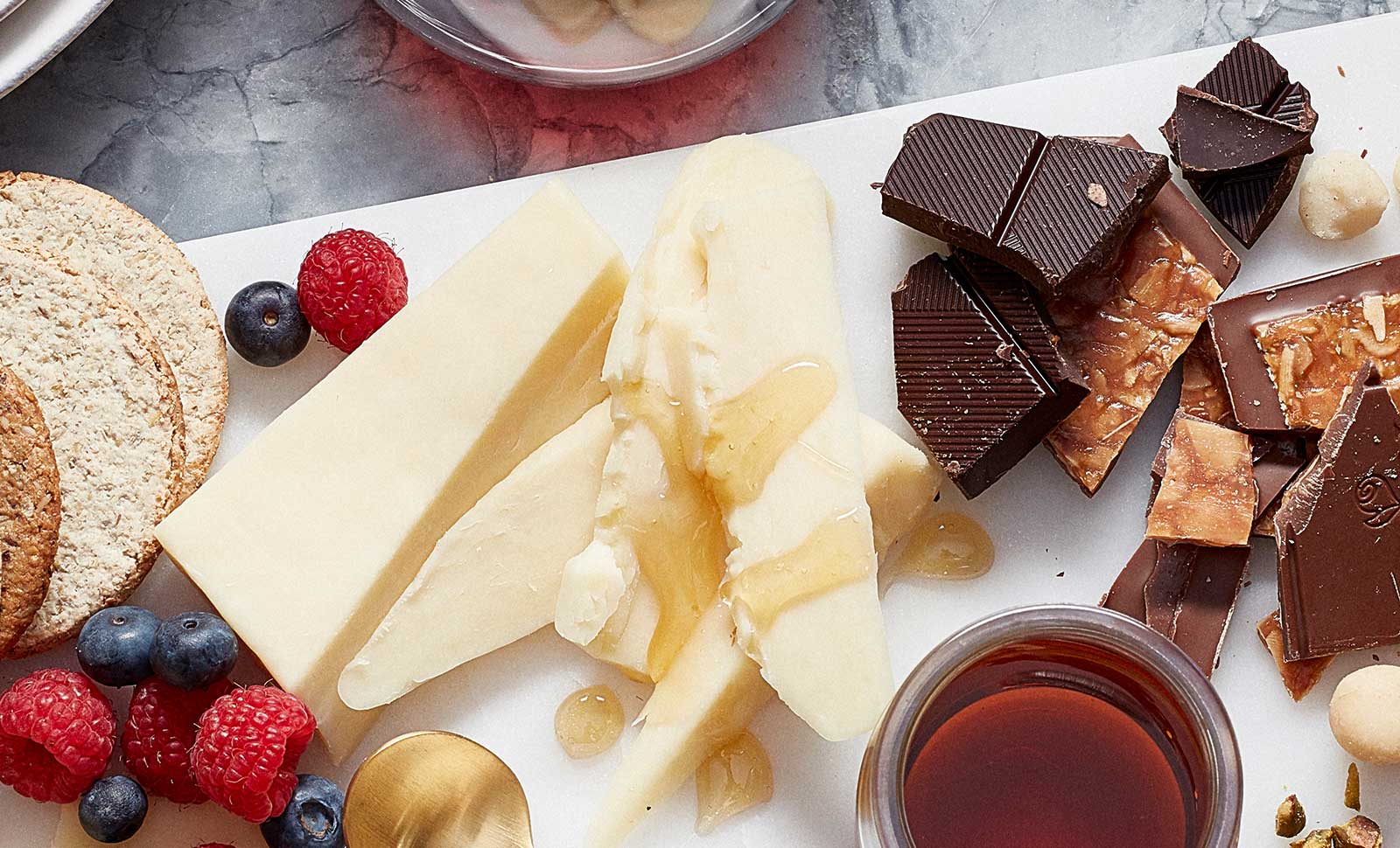 Pieces of artisan maple cheddar cheese served with fruit and pieces of dark chocolate.