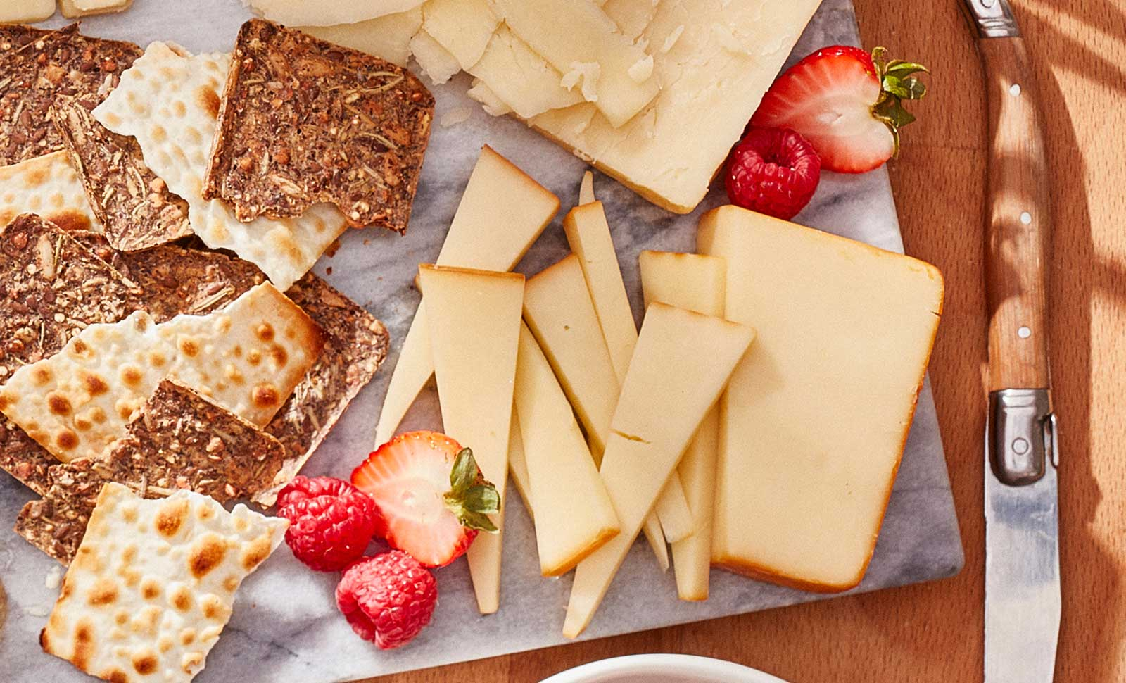Eight pieces of naturally smoked gouda cheese served on a plate with multigrain crackers.