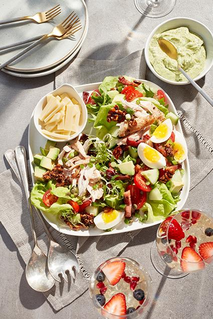 Salade de brunch colorée avec légumes feuilles variés, œuf tranché, cubes d'avocat, tomates et petit bol de tranches de fromage.