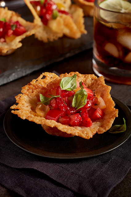An up-close shot of cheddar cheese cups with peppery strawberry salsa in front of plated food.