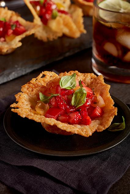 Plan rapproché de coupes de fromage cheddar avec salsa poivrée à la fraise devant une assiettée d'aliments.