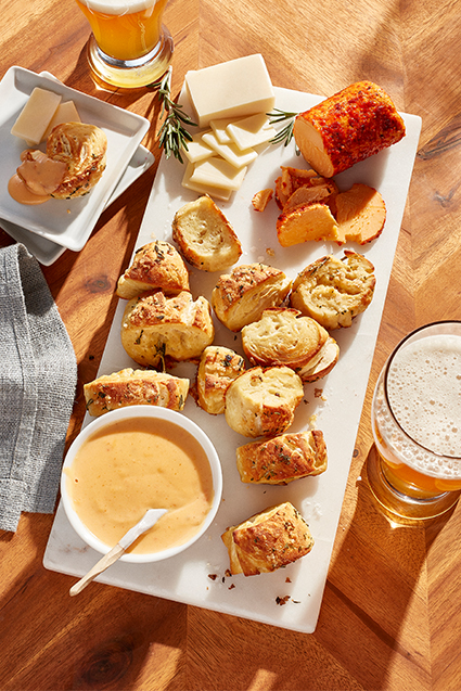 A board filled with cheesy herb pretzel bites, cheese logs and dips.