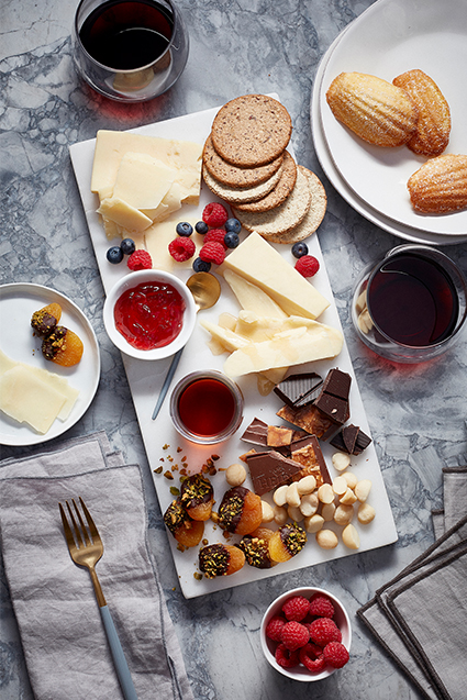 A charcuterie dessert board filled with slices of cheddar cheese, dark chocolate, nuts, jam, blueberries, raspberries and crackers.