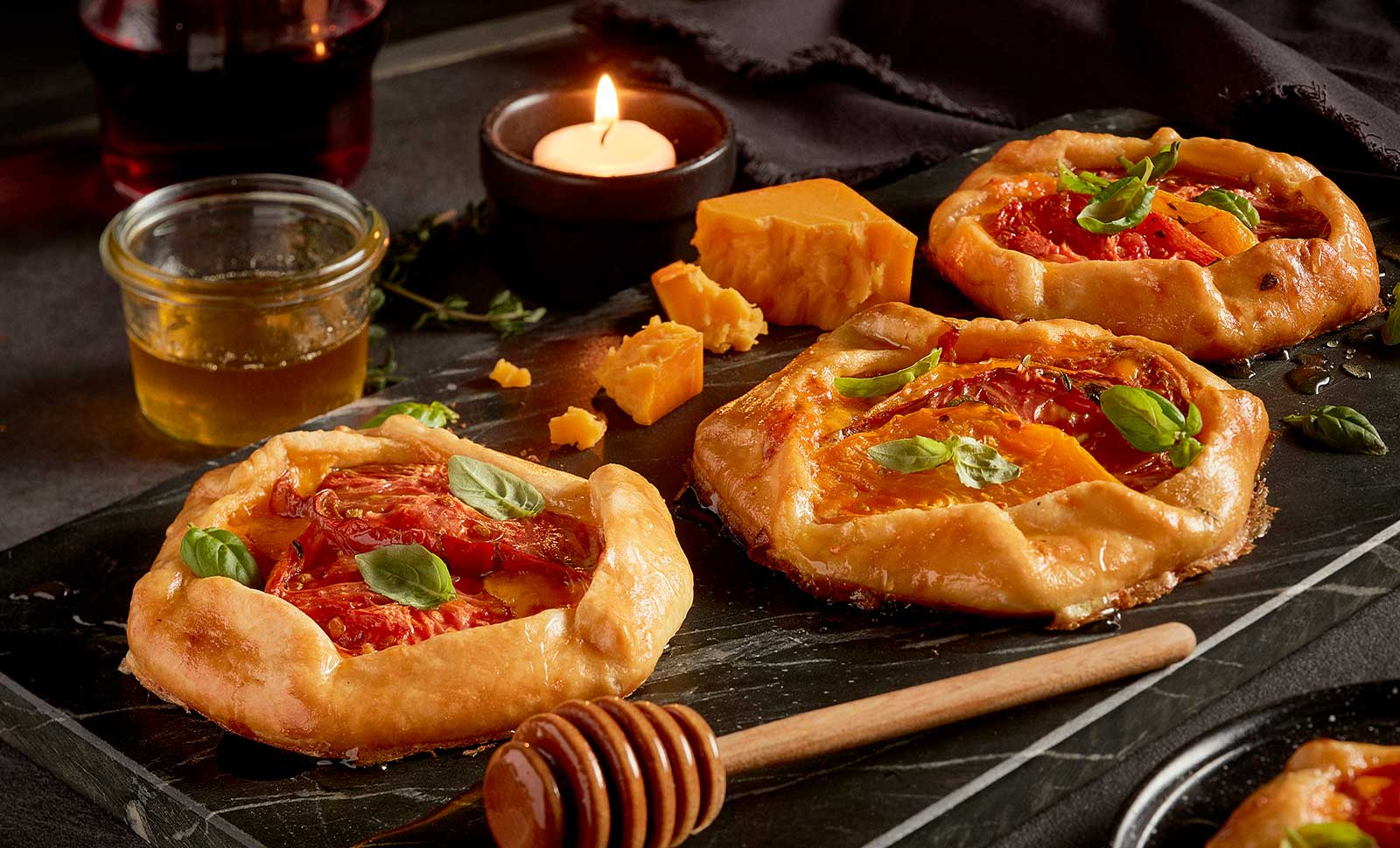 Three mini tomato cheese galettes with lavender honey along with pieces of cheddar cheese.