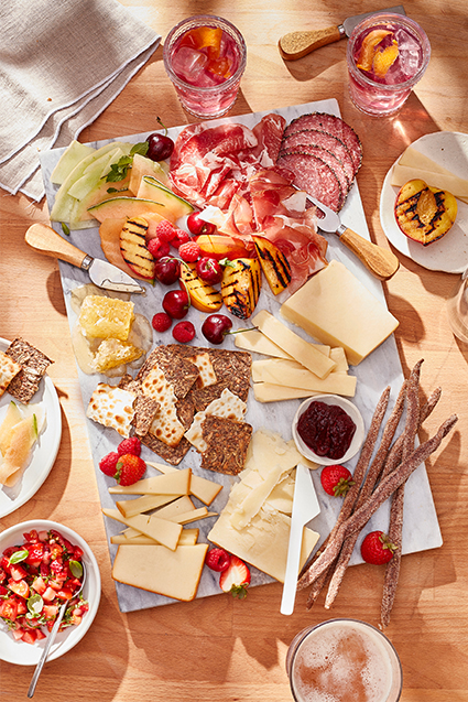 A summer inspired charcuterie board with aged cheddars, slices of salami and prosciutto, crackers, raspberries and cherries.