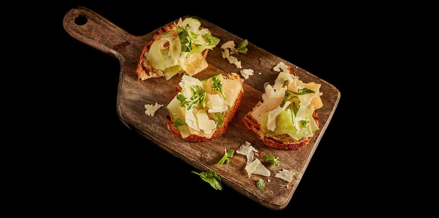 Three servings of cucumber melon caprese crostinis served on a wooden serving platter.
