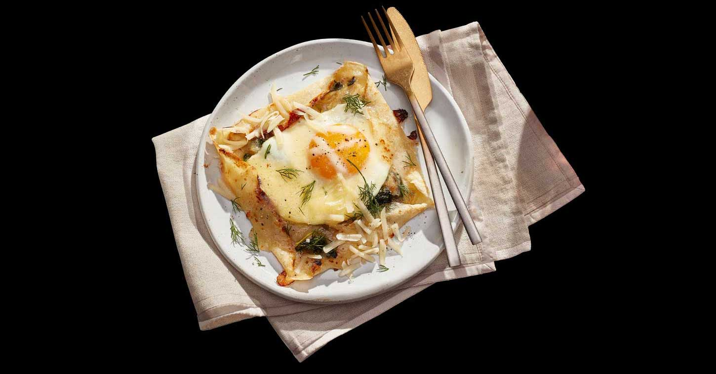 Open faced savoury cheddar herbs crepes on plate with a fork and knife.