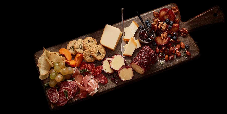 Plateau de charcuterie inspiré par l'automne avec bûche de fromage cheddar, fromage cheddar fumé, confiture, raisins, salami tranché, biscuits, amandes, bleuets et noix.
