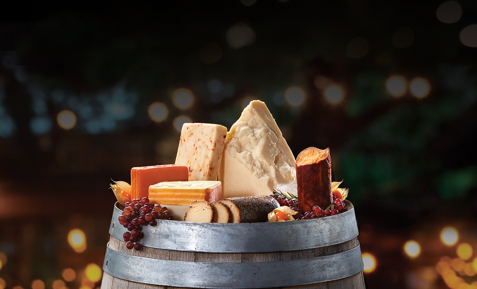 Assorted artisan, log and naturally smoked cheeses in the top of a wine barrel.