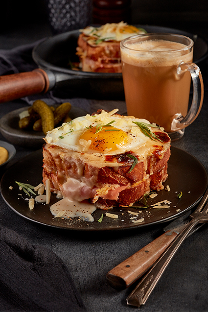 An up-close shot of a croque madam with a cappuccino and pickles in the background.
