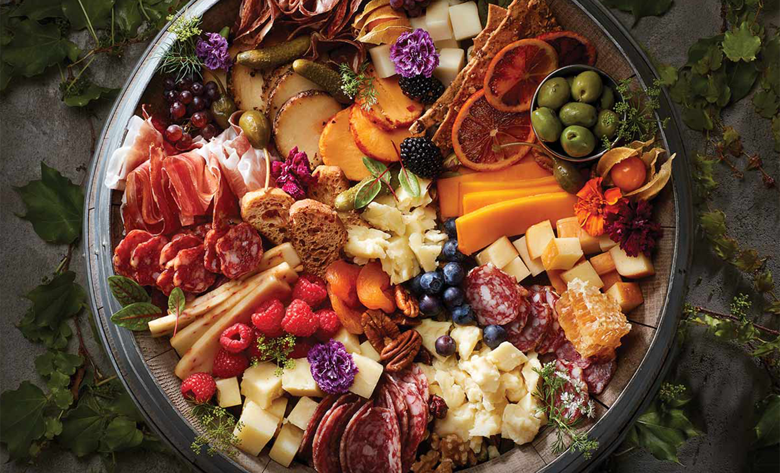 A wooden barrel topped with an assortment of cheeses, meats, fruits and breads