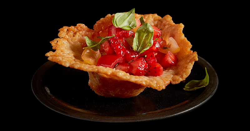 An up-close shot of cheddar cheese cups with peppery strawberry salsa.