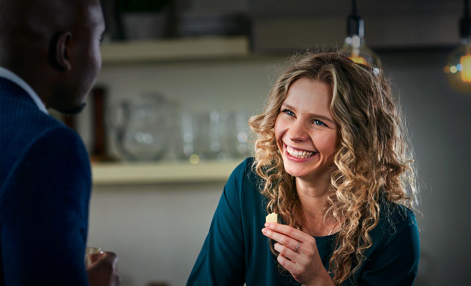 Femme dans la cuisine dégustant du fromage en discutant avec un homme.