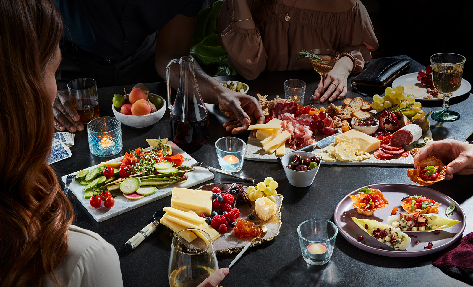 Four people around a table dressed in several platters of assorted cheeses, meats, fruits, vegetables, crackers, nuts, and cocktails.