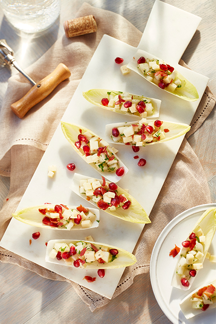 Seven pieces of endive leaves pear salad on a white plate served with a glass of white wine.