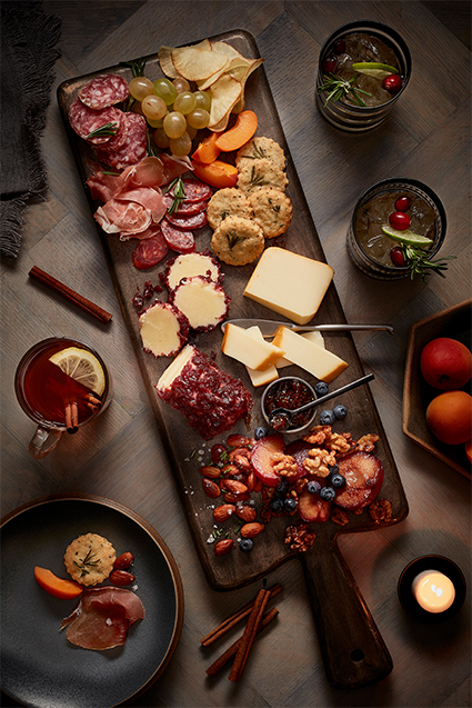 A fall inspired charcuterie board filled with slices naturally aged cheddar, cheddar logs, almonds, raspberries, blueberries, variety of sliced meats, grapes and biscuits.