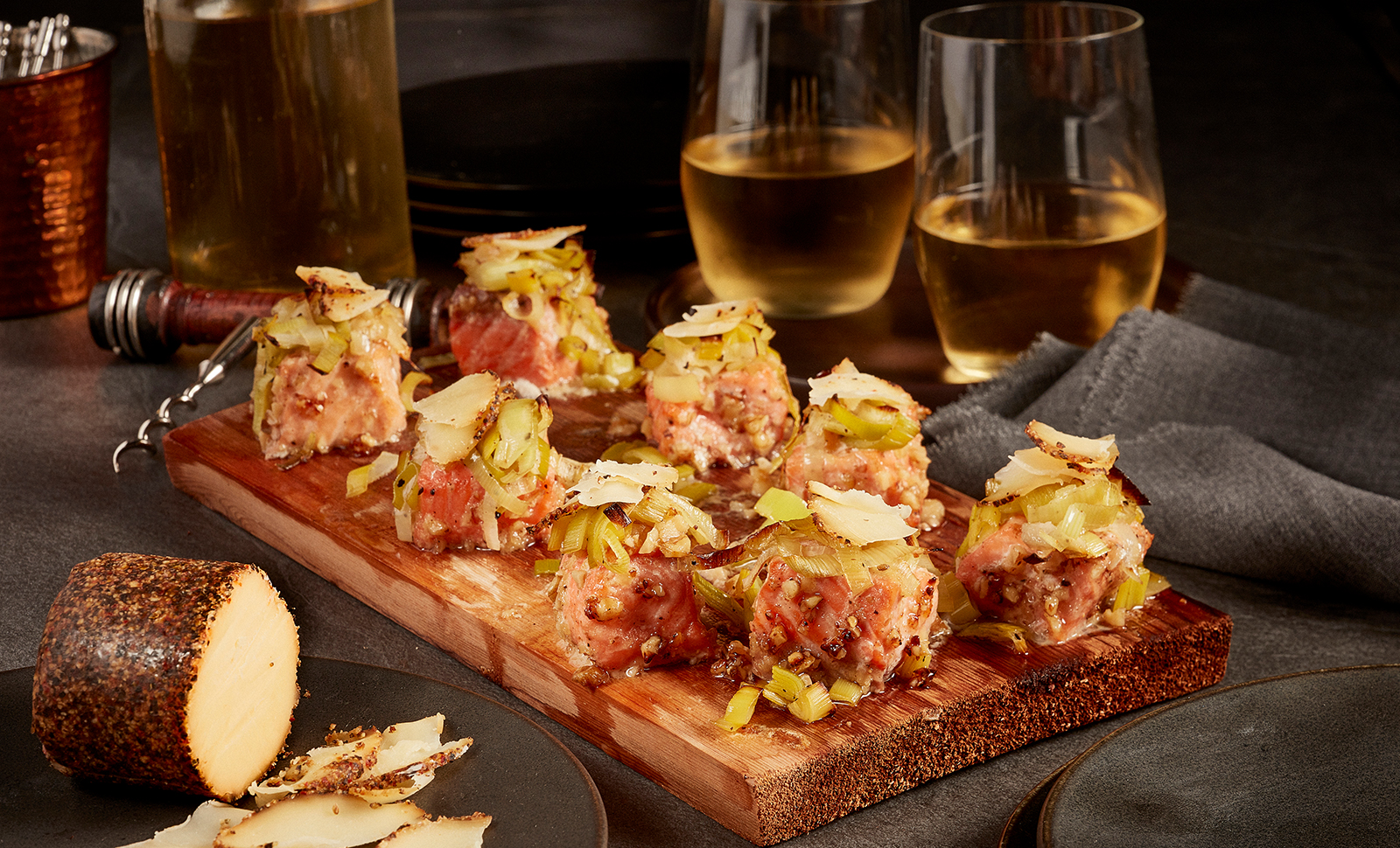 Maple walnut salmon bites served on a cedar plank with two glasses of white wine and Maple Cheddar with cracked black pepper cheese log.