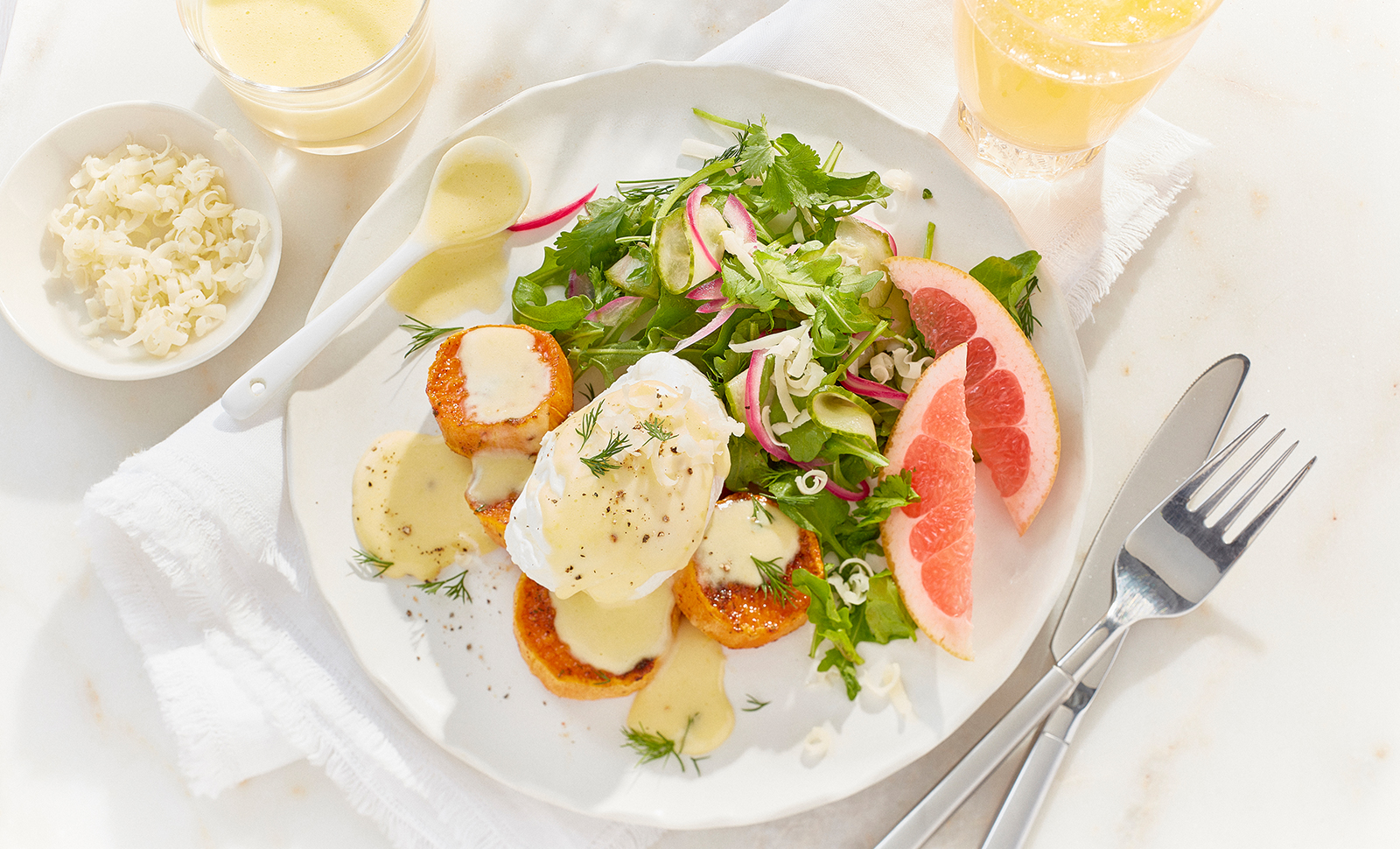 Eggs benedict on a plate served with leafy greens, orange slices and cheddar cheese shreds.