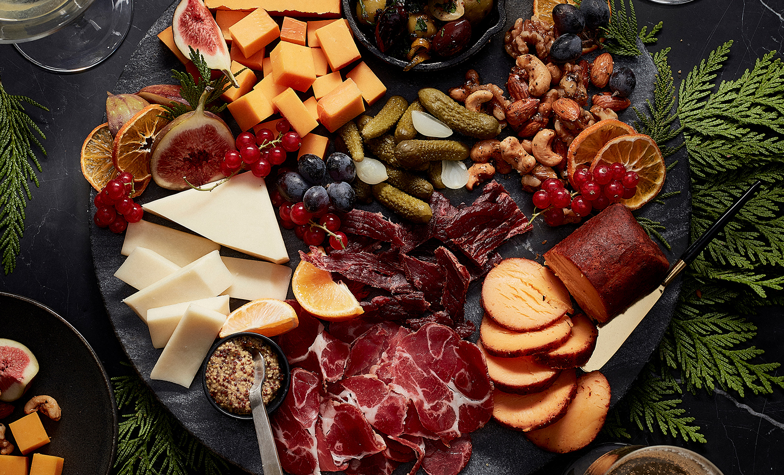 A winter inspired charcuterie board with a chipotle seasoned cheese log, cheddar cheese cubes, sweet pickles, mixed raw nuts, orange slices, grapes, blueberries and sliced meat.